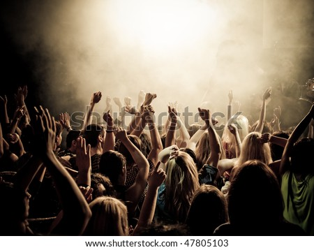 Crowd at a music concert, audience raising hands up - stock photo
