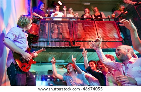 Crowd going wild during a live performance of a guitarist in a club - stock photo