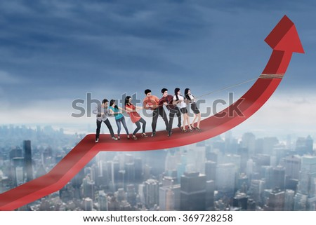 Crowd of businesspeople pulling arrow upward by using a rope above the city - stock photo