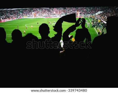 Crowd of footbal supporters and fans cheer at the stadium. - stock photo
