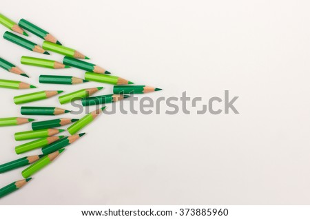 Crowd of green pens pointing to the right - team workshop, strategy, success, leadership concept with space for copy text - stock photo