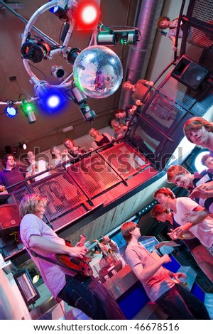 Crowd of people around a guitar player and saxophonist in a trendy nightclub - stock photo