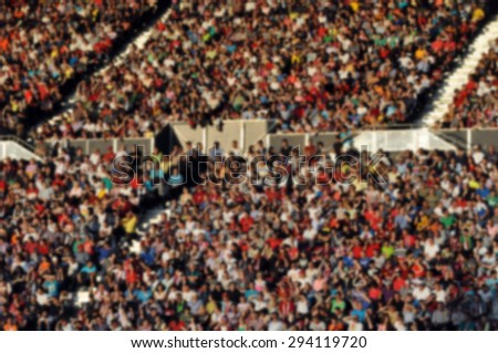 Crowd of people at a football match - blurred image - stock photo