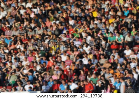 Crowd of people at a soccer match - blurred image - stock photo