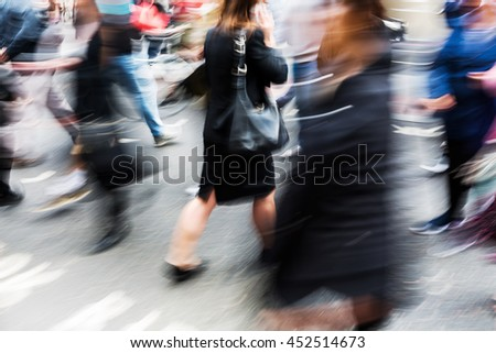 crowd of people crossing a street in the city in abstract motion blur
