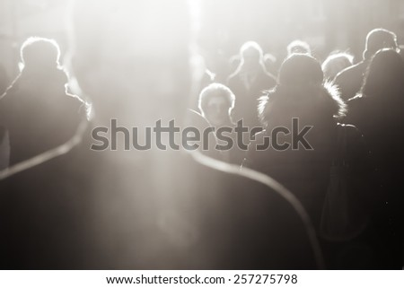 crowd of people in black and white in backlit - stock photo