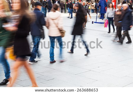 crowd of people in motion blur crossing a city square