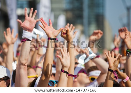 crowd of people raising their hands and have fun - stock photo