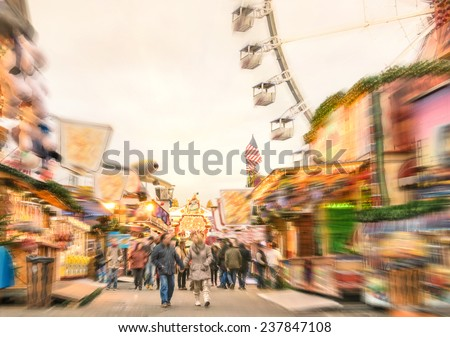 Crowd of people walking at luna park on a radial zoom defocusing - Multicolored fun stands at german Christmas market - Ferris wheel and colorful wooden houses at Berlin amusement area in winter time - stock photo