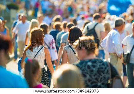 Crowd of people walking on the sunny and busy city street. Soft focus