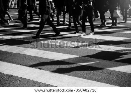 crowd of people walking on zebra crossing street - stock photo