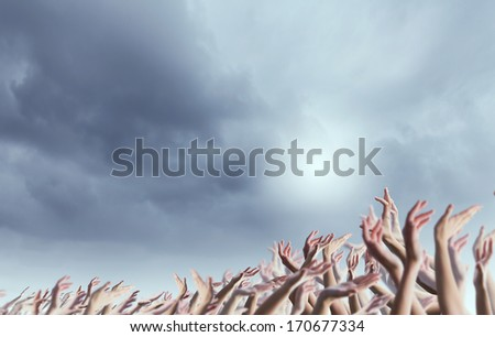 Crowd of people with hands raised up in to sky - stock photo