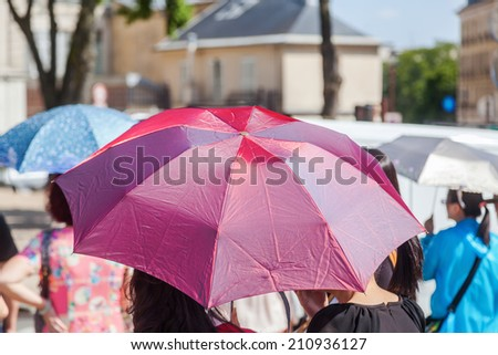 crowd of people with sun umbrellas