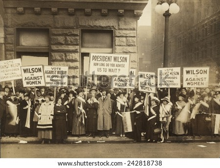 Crowd of women's suffrage supporters demonstrating with signs reading, 'Wilson Against Women,' in Chicago on October 20, 1916. Wilson withheld his support for Votes of Women until 1918. - stock photo