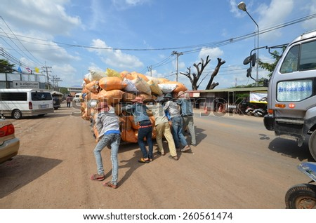 Crowd of young people pushing a cart overloaded bags across the border thailand cambodia.Photo taken on: December 11th, 2012