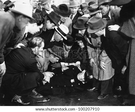 Crowd reviving police officer - stock photo
