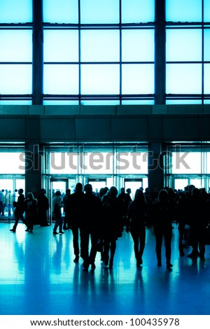 crowd silhouette inside modern building with wide blue enter hall window in exposition center - stock photo