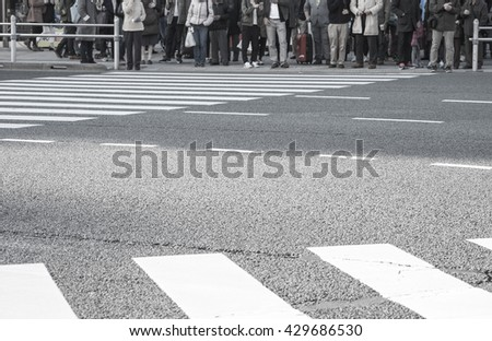 Crowded people waiting to cross the street at busy junction at downtown with selective focused point - stock photo