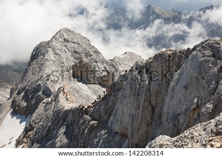 Crowded ridge. Many mountaineer on exposed ridge over the sea of clouds. Taken from the highest peak of Julian Alps (Triglav 2864 m); Slovenia.  - stock photo