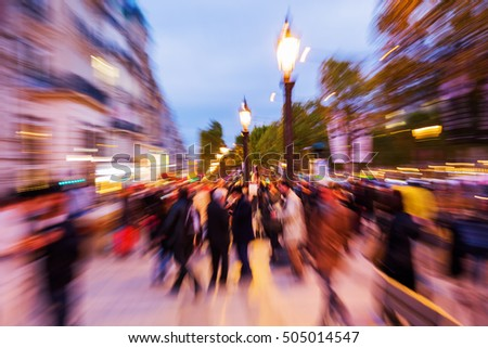 crowds of people at night on the Champs-Elysees in Paris, France, with zoom effect