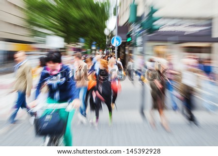 crowds of people with blurred zoom effect crossing the street in the city - stock photo