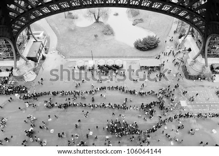 Crowds under Eiffel Tower in Paris France - stock photo