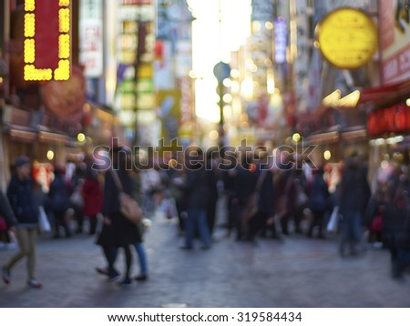 Crowds walk below the signs of Dotonbori. With a history reaching back to 1612, the district is now one of Osaka's primary tourist destinations. Abstract blur background .