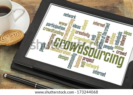 crowdsourcing word cloud on a  digital tablet with a cup of coffee - stock photo