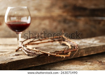 Crown of thorns and glass of wine on old wooden background - stock photo