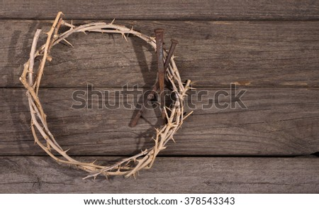 Crown of thorns and nails on a rustic wood surface