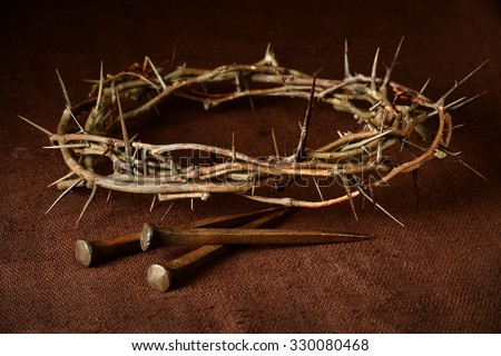 Crown of thorns and nails over vintage cloth - stock photo