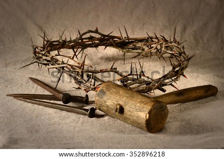 Crown of thorns and nails with mallet over cloth - stock photo