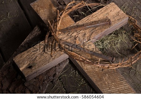 Crown of thorns and wood cross on a wooden surface