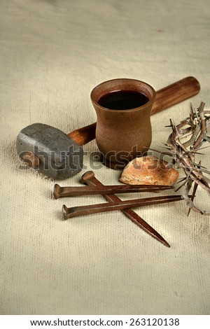 Crown of thorns, nails and mallet with communion elements over vintage cloth - stock photo