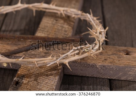 Crown of thorns with a cross on wood surface - stock photo
