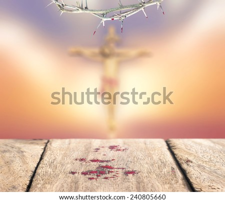 Crown of thorns with blood and drops of blood on old wooden floor over blurred Jesus with cross on a sunset. Thanksgiving, Christmas, Forgiveness, Repentance, Redemption, Redeemer, Eucharist concept. - stock photo
