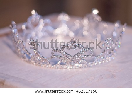 Crown on wooden box for wedding or pageant bokeh blur of crown in background.