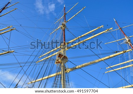 Crows nest, mast, and canvas sails can be seen in this closeup detail of an old time tall wooden sailing ship.