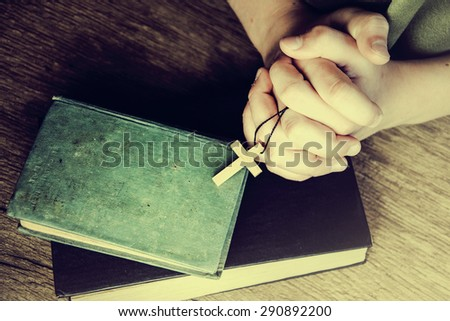 Crucifix in hand on the Holy Bible. - stock photo