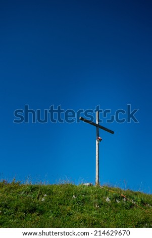 Crucifix on the top of the mountain in the middle of a meadow