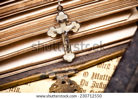 crucifix with jesus hanging on sides of opened historic bible,  - stock photo