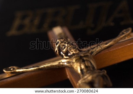 Crucifix with Jesus on black leather Bible. - stock photo