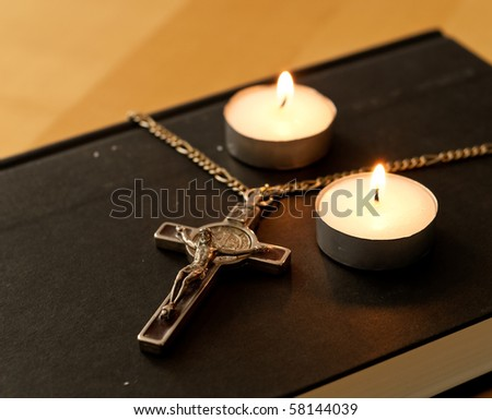 Crucifix with Lit Tea Candles on Bible - stock photo