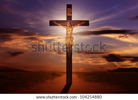 Crucifixion Jesus on the cross with sun rays on the road - stock photo