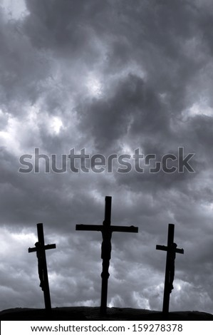 Crucifixion of Jesus on the cross with storm clouds - stock photo