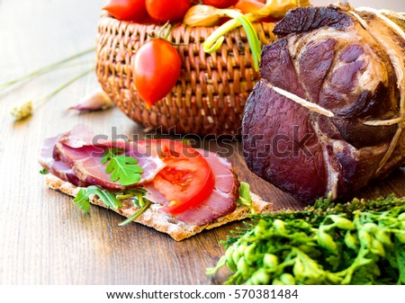 Crude, dried bacon or ham with sandwich, vegetables and herbs on wooden board