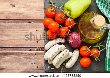 crude sausages and vegetables on a table, selective focus
