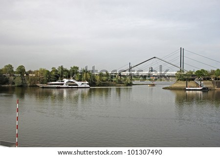 Cruise boat entering Duesseldorf harbour from the River Rhine - stock photo