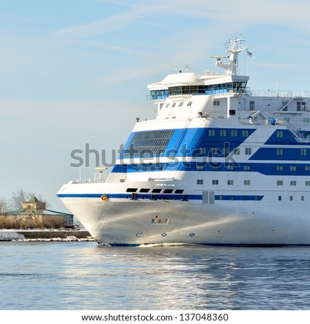 cruise ferry ship with lighthouse at the background - stock photo