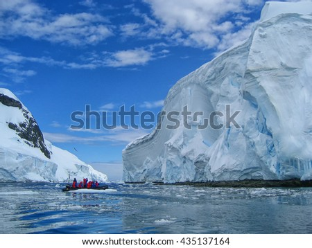 Cruise passengers in an inflatable rib study the amazing colors and shapes of a large iceberg in Antarctica.